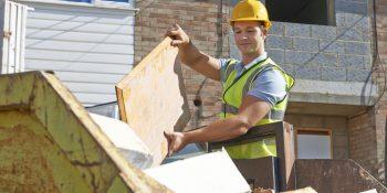 Construction worker putting rubbish in skip bin